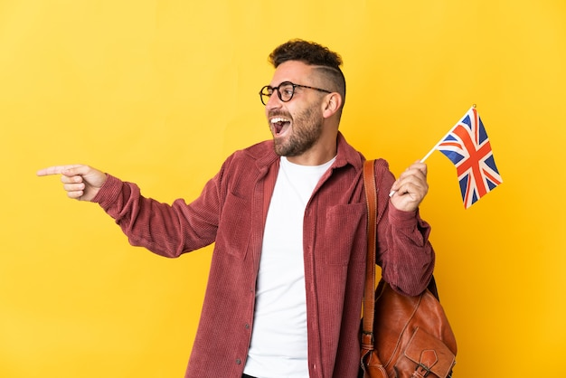 Caucasian man holding an united kingdom flag isolated on yellow background pointing finger to the side and presenting a product