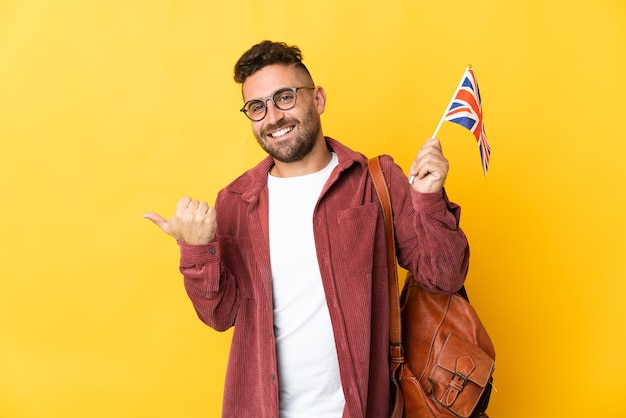 Caucasian man holding an united kingdom flag isolated on yellow background pointing to the side to present a product