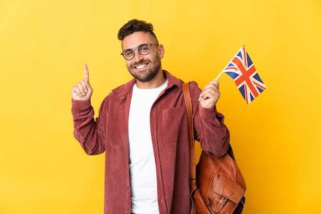 Caucasian man holding an united kingdom flag isolated on yellow background pointing up a great idea
