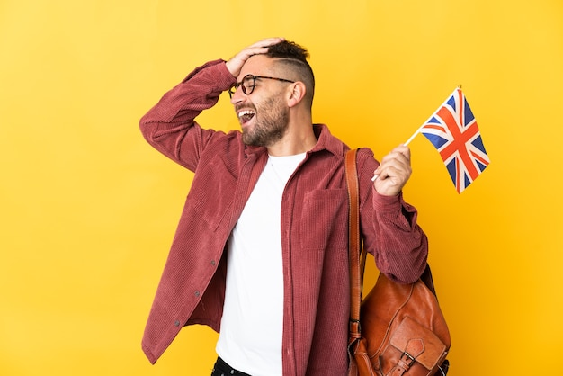 Caucasian man holding an united kingdom flag isolated on yellow background smiling a lot