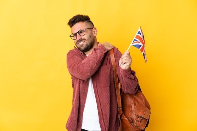 Caucasian man holding an united kingdom flag isolated on yellow background suffering from pain in shoulder for having made an effort