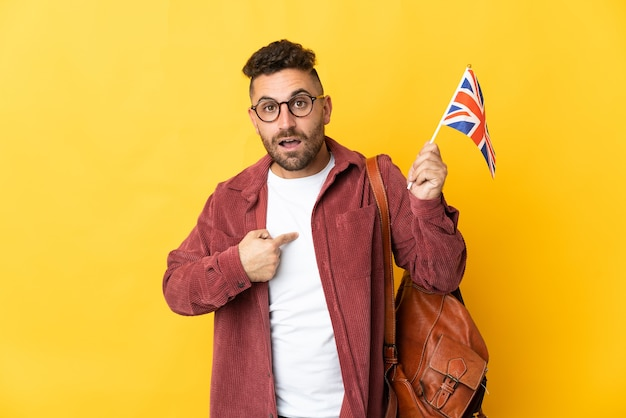 Caucasian man holding an united kingdom flag isolated on yellow wall with surprise facial expression