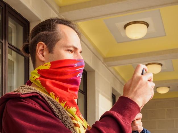 얼굴에 반다나를 두른 백인 남자가 스마트폰으로 뭔가 사진을 찍고 있다