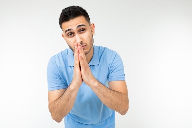 Кавказский мужчина в голубой футболке искренне просит что-то на белом изолированном фоне.