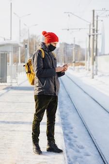 電車とテキストメッセージを待っている駅で暗いジャケットと赤い帽子をかぶった白人男性