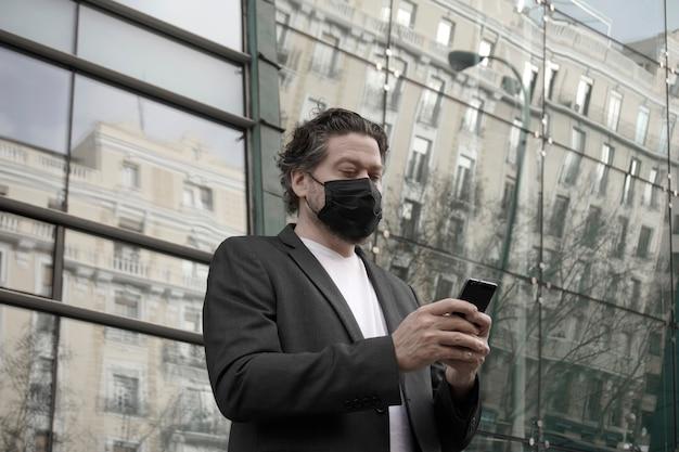 Кавказский мужчина в пиджаке и маске с мобильным телефоном в руке перед стеклянным зданием