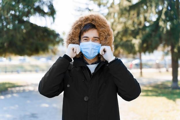 Кавказский мужчина в синей медицинской маске надевает стерильную маску на лицо