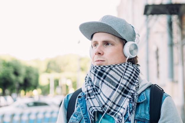 헤드폰 백인 남자는 음악을 듣고 도시 주변을 산책