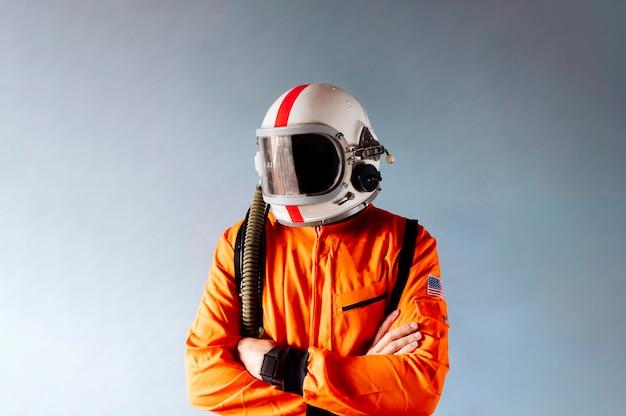 Кавказский мужчина в оранжевом защитном костюме со скрещенными руками удивленно искоса смотрит на звезды. изолированный синий фон