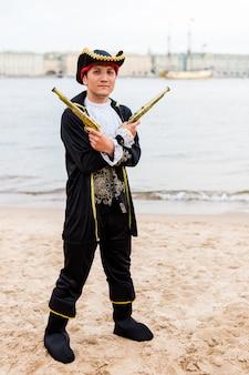 해적 의상 백인 남자가 그의 앞에 총을 들고 무기를 건 crossed 다.