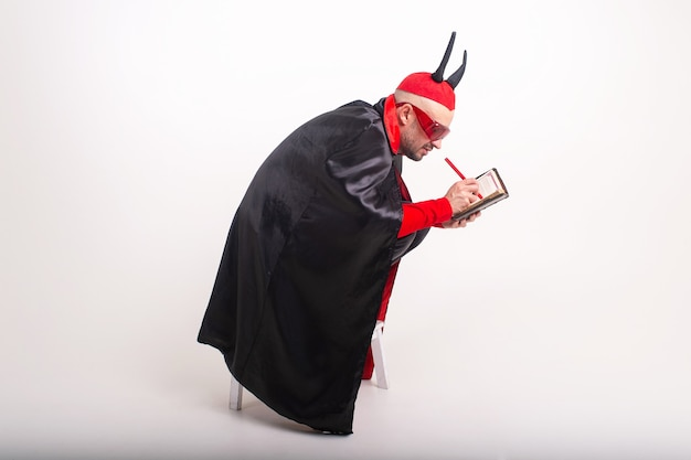빨간 선글라스와 흰색 스튜디오 배경 위에 펜 및 노트북 할로윈 의상 백인 남자.
