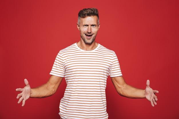 Кавказский мужчина в полосатой футболке жестикулирует и демонстрирует размер с copyspace, изолированным на красном