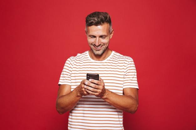赤で隔離の携帯電話を笑顔で保持している縞模様のtシャツの白人男性