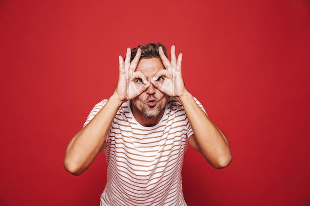 Кавказский мужчина в полосатой футболке улыбается и смотрит сквозь дыры, сделанные пальцами, изолированными на красном