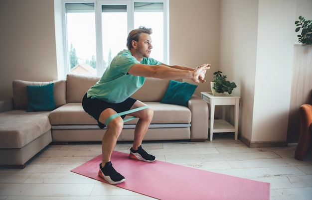 Caucasian man is doing fitness at home using special bands on the floor while squatting