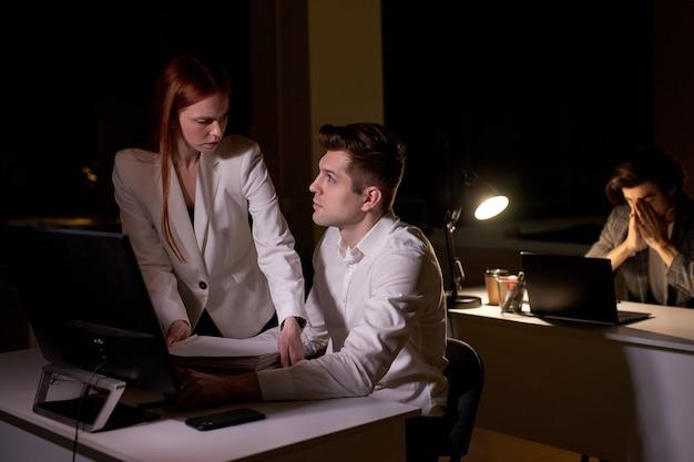 백인 남자는 밤에 사무실에서 그녀를 보고 있는 여성 동료에게 부분적입니다. 시작 사무실에서 함께 일하는 동료들에 대한 측면 보기, 공식적인 옷을 입은 남자, 컴퓨터와 함께 책상에 앉아 있는 남자