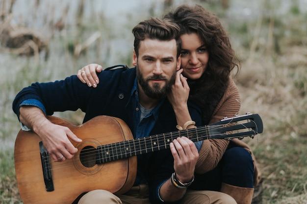 Кавказский мужчина играет на гитаре с женщиной у озера