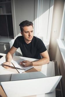 白人男性がノートパソコンを使用して自宅から離れた場所で作業し、窓の近くで何かを考えています