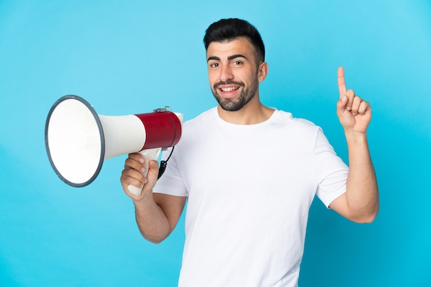 Caucasian man over isolated blue wall holding a megaphone and pointing up a great idea