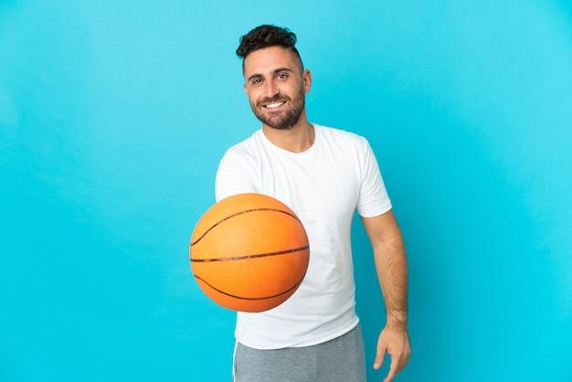 Кавказский человек, изолированные на синем фоне, играет в баскетбол