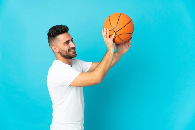 バスケットボールをしている青い背景に分離された白人男性