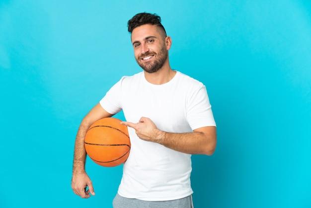 青でバスケットボールをし、側面を指している白人男性