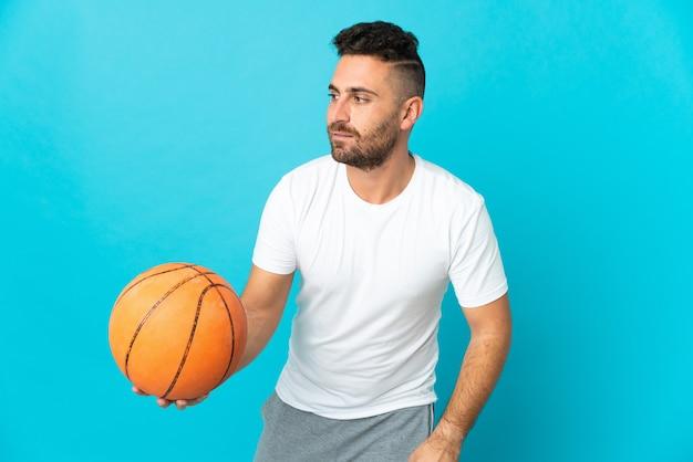 バスケットボールをしている青に孤立した白人男性
