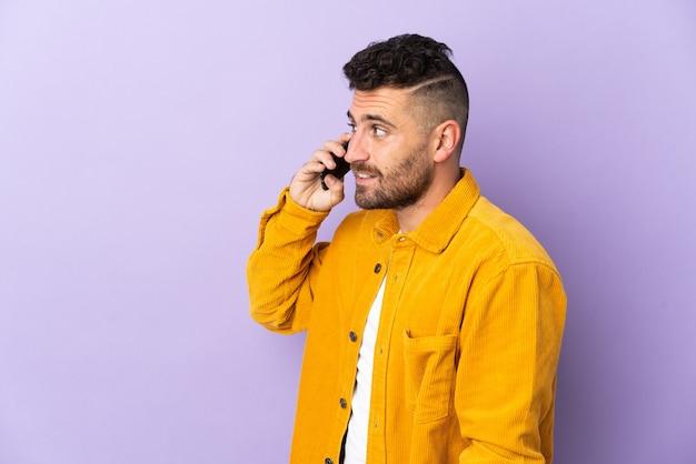 誰かと携帯電話との会話を維持している紫色の背景に孤立した白人男性