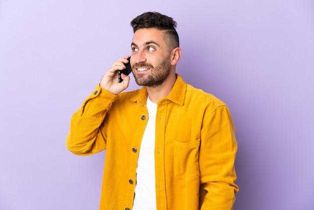 누군가와 휴대 전화로 대화를 유지하는 보라색 배경에 고립 된 백인 남자