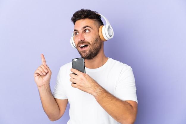 모바일 및 노래와 보라색 배경 듣는 음악에 고립 된 백인 남자