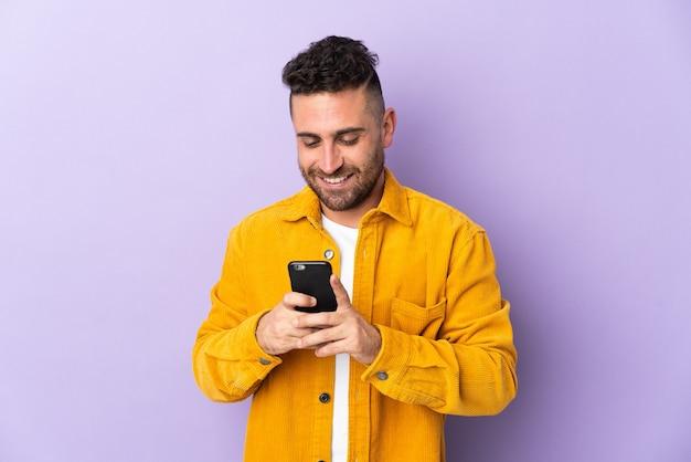携帯電話でメッセージやメールを送信する紫色の背景に孤立した白人男性