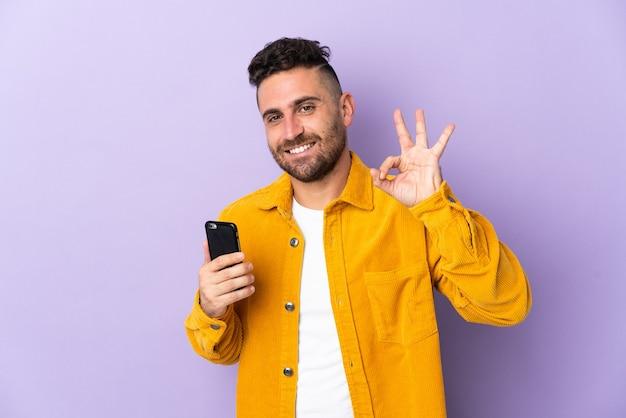 Кавказский человек изолирован на фиолетовом фоне с помощью мобильного телефона и делает знак ок