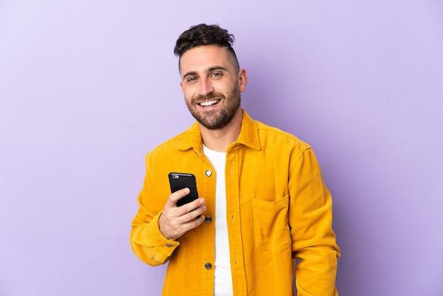 携帯電話を使用して紫色の背景に分離された白人男性