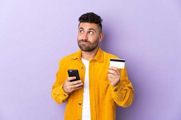 Кавказский мужчина изолирован на фиолетовом, покупая с помощью мобильного телефона с помощью кредитной карты, думая