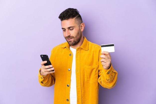 Кавказский мужчина изолирован на фиолетовом, покупая с мобильного телефона с помощью кредитной карты