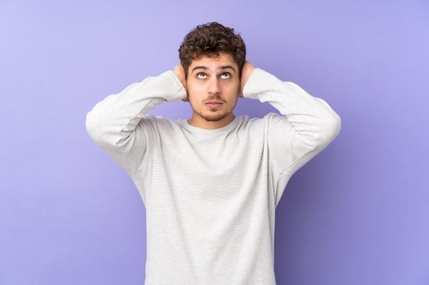 Кавказский мужчина изолирован на фиолетовом разочарованном и закрывает уши