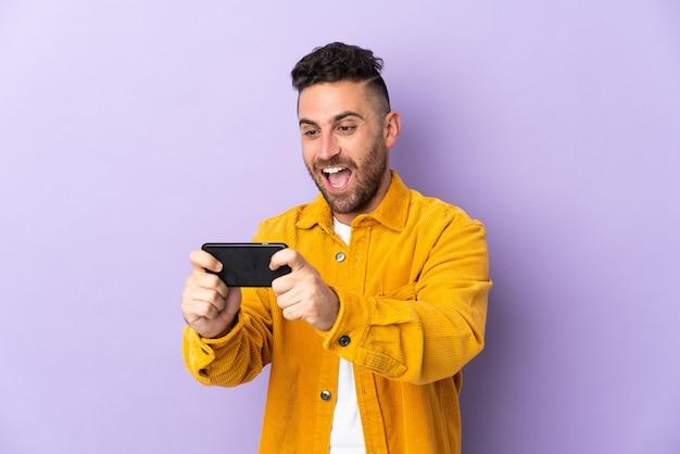 Кавказский мужчина изолирован на фиолетовом, играя с мобильным телефоном
