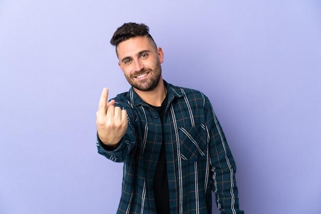 Кавказский мужчина изолирован на фиолетовой стене, делая приближающийся жест