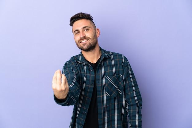 이탈리아 제스처를 만드는 보라색 벽에 고립 된 백인 남자