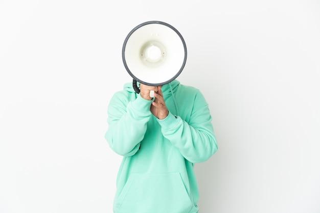 뭔가 발표하기 위해 확성기를 통해 외치는 흰 벽에 고립 된 백인 남자