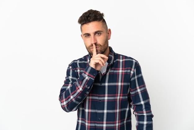 입에 손가락을 넣어 침묵 제스처의 기호를 보여주는 흰 벽에 고립 된 백인 남자
