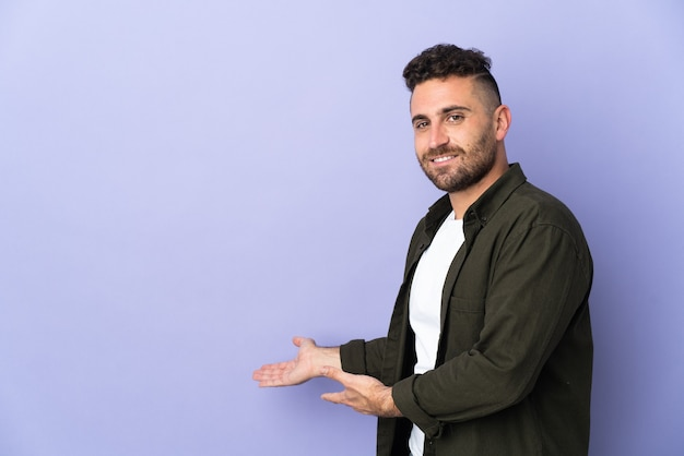 Caucasian man isolated on purple background extending hands to the side for inviting to come