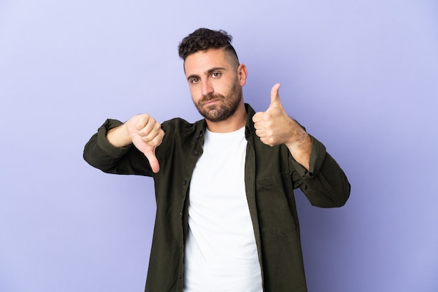 Caucasian man isolated on purple background making good-bad sign. undecided between yes or not