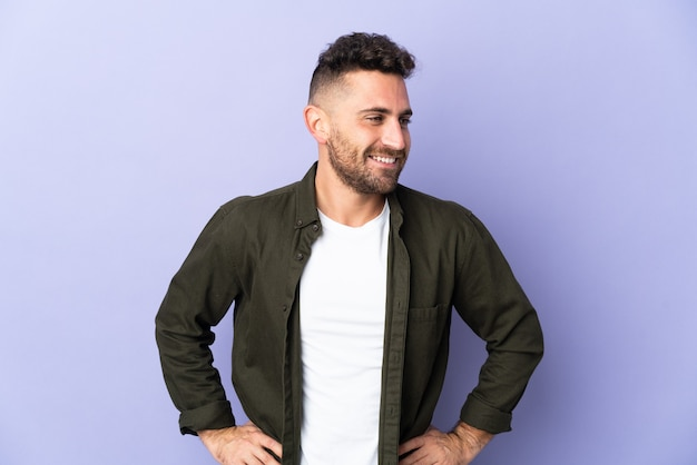 Caucasian man isolated on purple background posing with arms at hip and smiling