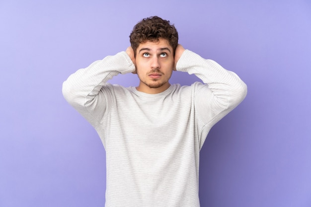 Caucasian man isolated on purple frustrated and covering ears