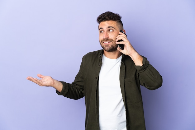 Caucasian man isolated on purple wall keeping a conversation with the mobile phone with someone