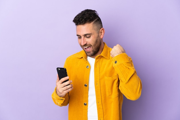 Caucasian man isolated on purple wall using mobile phone and doing victory gesture