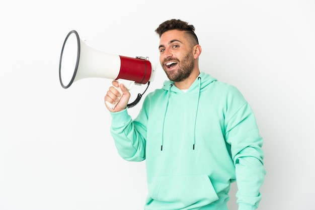 Caucasian man isolated on white background holding a megaphone and smiling
