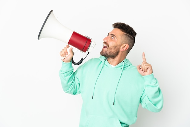 Caucasian man isolated on white background shouting through a megaphone to announce something in lateral position