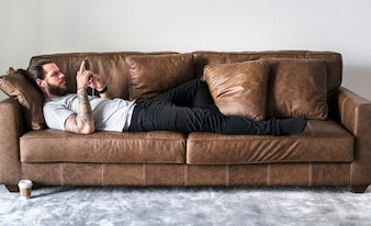 Caucasian man listening to music on a couch